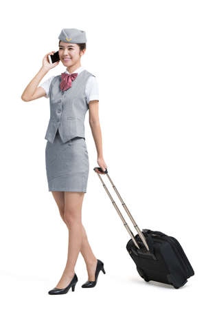 Smiling Chinese airline stewardess with wheeled luggage making a phone call