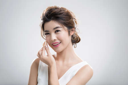 Young Chinese woman applying facial powder
