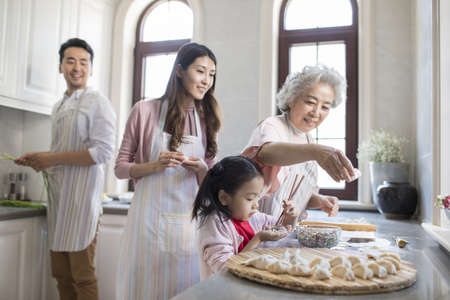 Cheerful Chinese family making dumplings in kitchen