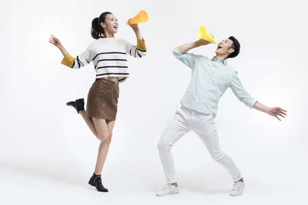 Young Chinese couple shouting through megaphones LANG_EVOIMAGES