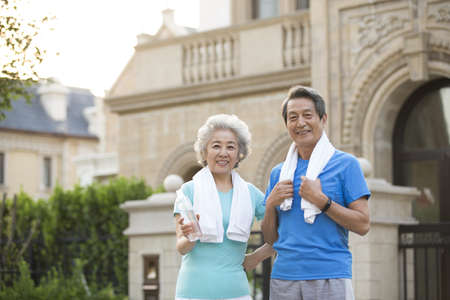 Senior Chinese couple with towel and water after jogging LANG_EVOIMAGES