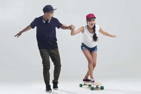 Cheerful young couple skateboarding