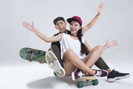 Portrait of cheerful young Chinese couple sitting on skateboard