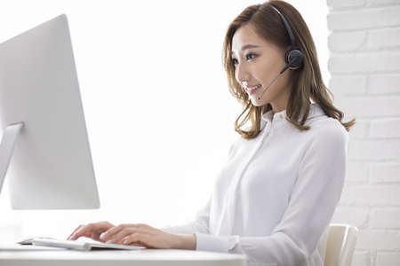 Cheerful young Chinese businesswoman with headset in office