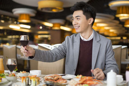 Cheerful young Chinese man having buffet dinner