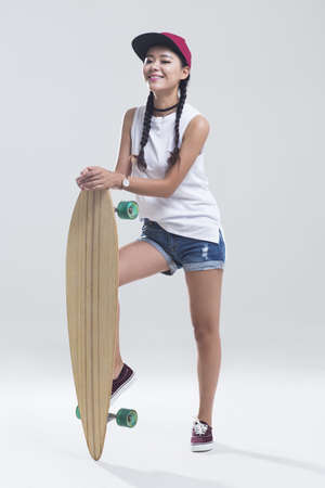Cheerful young Chinese woman with skateboard