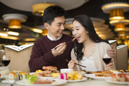 Cheerful young Chinese couple having buffet dinner LANG_EVOIMAGES
