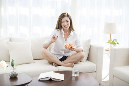 Cheerful young Chinese woman eating fruit salad on sofa LANG_EVOIMAGES