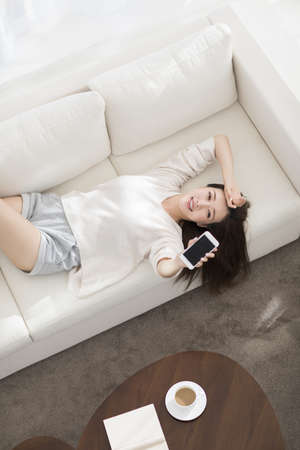 Cheerful young Chinese woman showing a smart phone at home