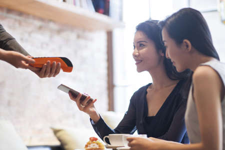 Chinese friends paying with smart phone in café