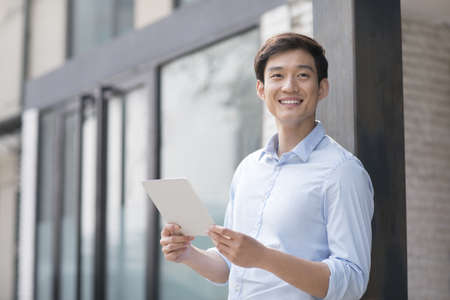 Young Chinese businessman holding a digital tablet outdoors LANG_EVOIMAGES