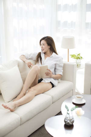 Cheerful young Chinese woman reading a book at home LANG_EVOIMAGES