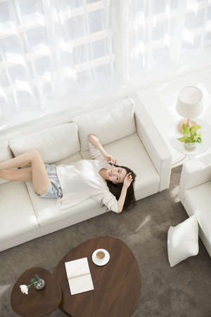 Cheerful young Chinese woman talking on cell phone at home LANG_EVOIMAGES