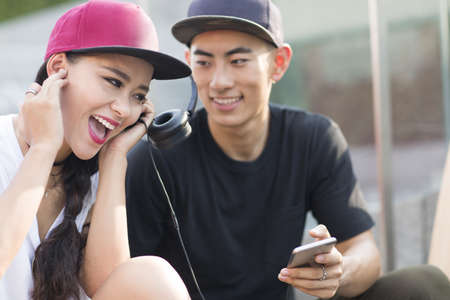 Cheerful young Chinese couple with skateboard listening to music on stairs