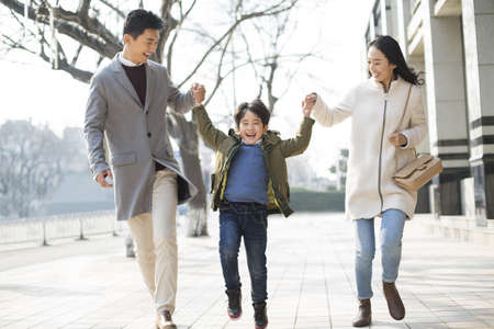 Cheerful young Chinese family holding hands walking