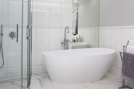 The bathroom has a modern style and marble tiles