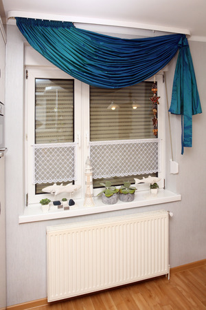A window with a beautiful curtain in a useful kitchen