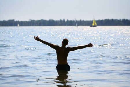 A very happy man stands in the water with his hands raised