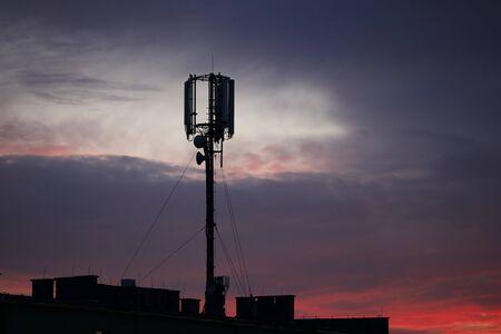 Internet mast on sunset background