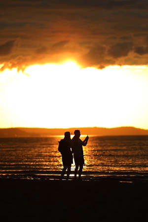 People are taking pictures of themselves against the setting sun on the seashore Standard-Bild