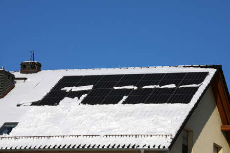 The solar panel is partially covered with snow in winter