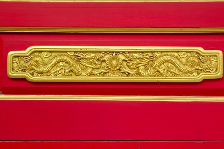 gold dragon decorate on red door at wat leng noei yi 2 thailand photo