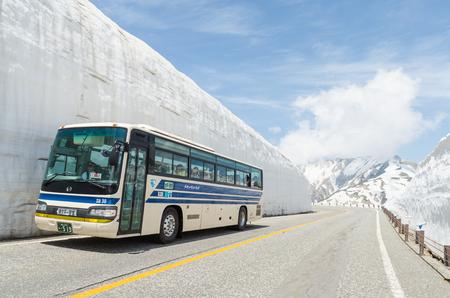 Toyama, Japón - 20 de mayo de 2016: Movimiento de autobuses de turistas a lo largo de la pared de nieve de los Alpes de Japón en la ruta alpina tateyama kurobe