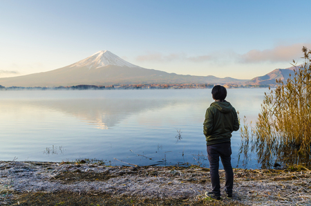Asian man traveler looking sunrise and mount fuji reflect on water in morning at kawaguchiko lake japan Stock Photo