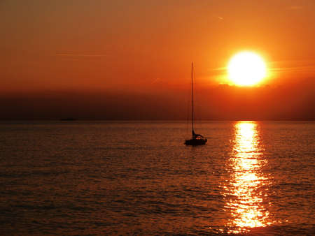 Quiet bright sunset on seascape with sailboat Stock Photo