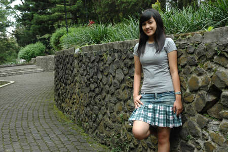 simple girl: young lady stand up beside rock wall