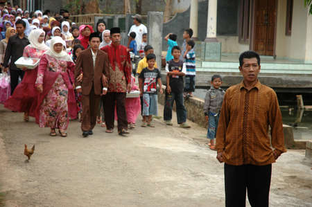 cikijing, west java, indonesia - july 10, 2011  groom and his big family are walking together into the bride house