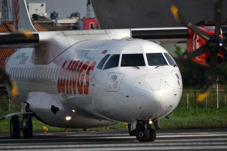 manoeuvre: bandung, indonesia-june 16, 2014  Wings Air airplane taking manoeuvre on husein sastranegara airport bandung  Editorial