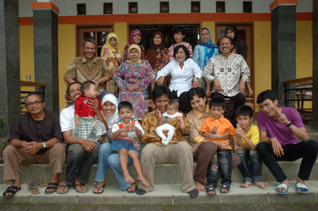 gathering: bandung, indonesia-december 19, 2010  large group of family gathering together in front of house