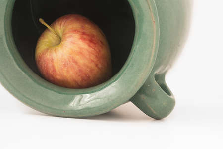man made object: close up view of a red apple inside the greenish earthen jar isolated on white background.