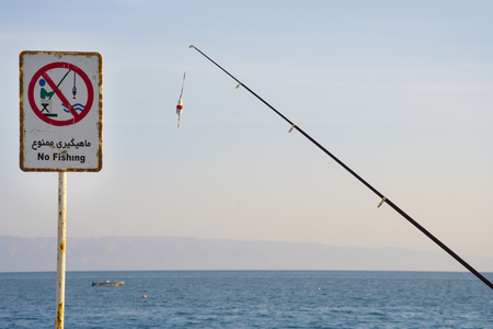 rod sign: A fishing rod beside the no fishing sign on pier declares fishing to be illegal in this body of water. People catching fishes  under a sign that says No fishing at this place.
