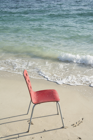 soapy: An Empty Single Red Chair at Tropical Coastline Beside Ocean Soapy White Waves Stock Photo