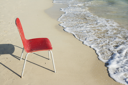 aloneness: An Empty Single Red Chair at Tropical Coastline Beside Ocean Soapy White Waves Stock Photo