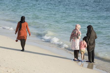 femmes muslim: Groupe des femmes musulmanes Contempler et profiter de leur temps à la plage Banque d'images