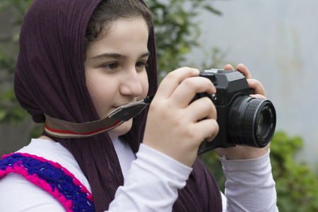 strapped: Young Little Girl Is Taking Photograph by An old Analogue Camera Strapped on Her Neck Stock Photo
