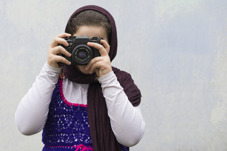 take a history: Young Little Girl Is Taking Photograph by An old Analogue Camera Strapped on Her Neck.