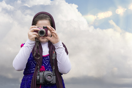 strapped: Young Little Girl Is Taking Photograph by Point and Shoot Digital Camera In front of Blue Sky with Clouds. An old Analogue Camera Strapped on Her Neck. Selection Path Included. Stock Photo