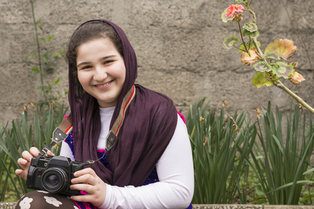 strapped: Smiling Young Little Girl Is Strapped an Analogue Camera on Her Neck in Flower Garden