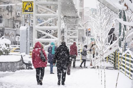 Dr Fatemi street Tehran, IRAN - January 28, 2018 People going up to overpass bridge to moving other side of street in snowy day. Редакционное