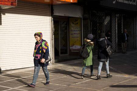Tehran, IRAN - March 8, 2018 Muslim woman walking trhogh Vali-asr street. Редакционное