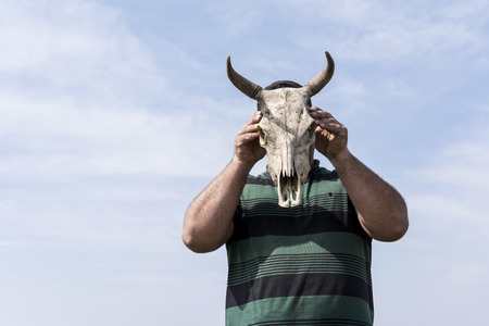 Young man holding a cow skull in front of his head in front of blue sky, low angle view point Stock Photo
