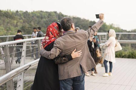 Tehran, IRAN - April 9, 2018 Group fo family taking selfi at Ab-o-atash park ( Tabiat bridge)