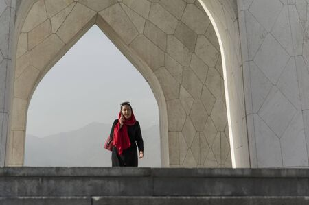TEHRAN, IRAN - 7 May  2018 Muslim woman walking under Azadi tower formerly known as the Shahyad tower is a monument located at Azadi square and is an architectural landmark of Tehran