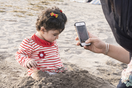 Little kid playing at beach with sand and her mother taking photos by smartphone Фото со стока