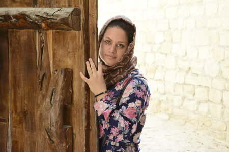 Portrait of a young muslim woman behind wooden door, underground kariz city kish island