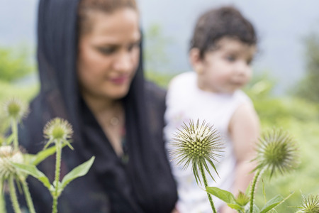Nature exploration concept, mother and young child in outdoor environment. Focus at foreground plants 版權商用圖片